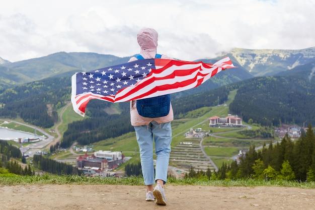 Vista traseira da viagem em pé no topo da colina, segurando a bandeira dos eua nas costas dela, vestindo jeans, tênis e jaqueta rosa