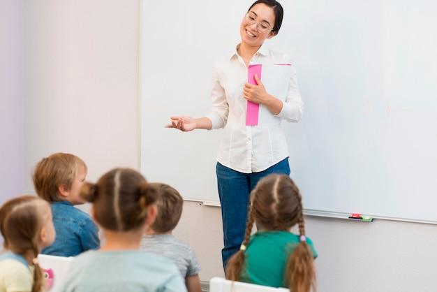 Vista traseira das crianças prestando atenção ao professor durante a aula