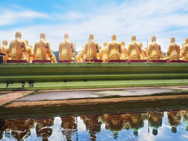 Vista traseira das estátuas de monge dourado sentado com reflexo de água no templo público