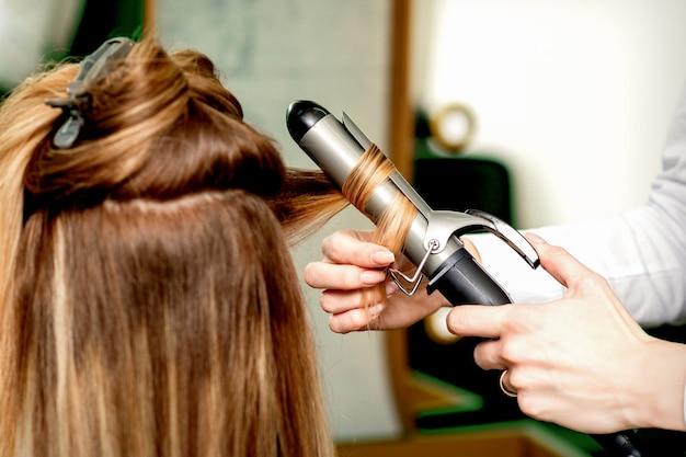 Vista traseira das mãos de cabeleireiras femininas ondulando o cabelo das mulheres com modelador em um salão de cabeleireiro
