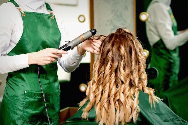 Vista traseira das mãos de uma cabeleireira enrolando o cabelo feminino com modelador em um salão de cabeleireiro