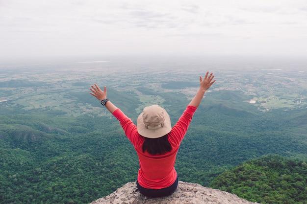 Vista traseira das mulheres sentadas no penhasco e empurre as mãos contra a montanha e a árvore