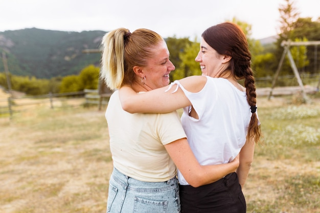 Vista traseira das namoradas, sorrindo e se abraçando na zona rural. melhor amigo, conceito de amor e amizade.