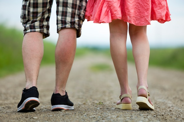 Vista traseira das pernas da jovem magro em vestido vermelho e homem de short caminhando juntos pela estrada de terra num dia ensolarado de verão no fundo desfocado.