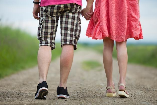 Vista traseira das pernas de jovem magro no vestido vermelho e homem de short caminhando juntos pela estrada de terra num dia ensolarado de verão na cena borrada.