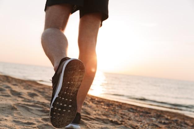 Vista traseira das pernas de um esportista correndo na areia