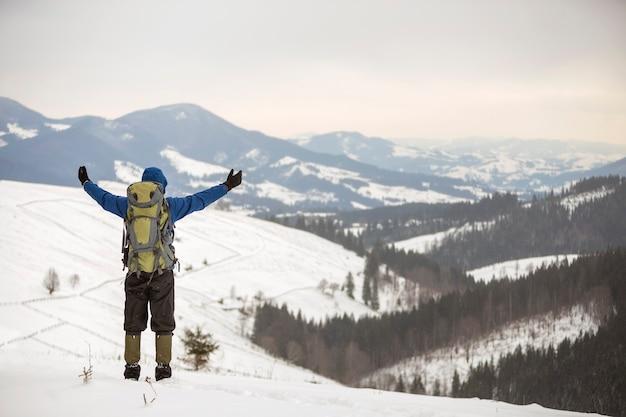 Vista traseira de alpinista com roupas quentes e mochila em pé com os braços erguidos na montanha