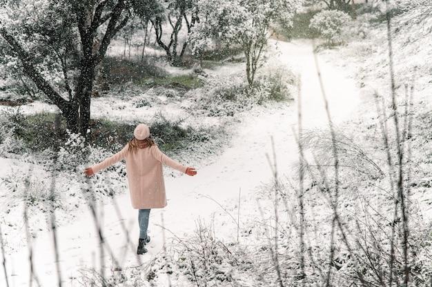 Vista traseira de alto ângulo de uma mulher anônima caminhando com os braços estendidos ao longo do caminho de neve e desfrutando de um passeio na floresta no inverno