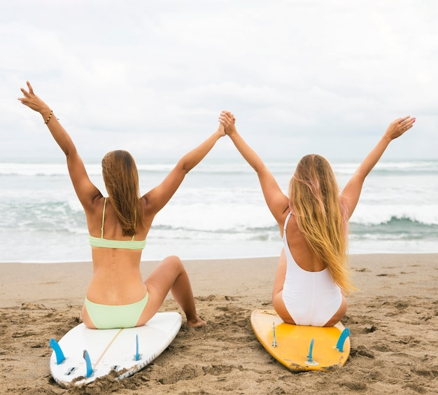 Vista traseira de amigas na praia em pé na prancha de surf com as mãos para cima