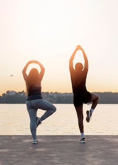 Vista traseira de amigas praticando ioga ao pôr do sol