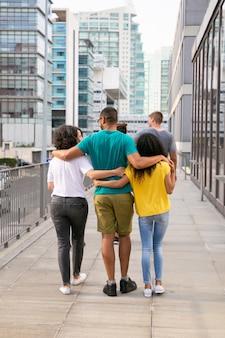 Vista traseira de amigos andando na rua