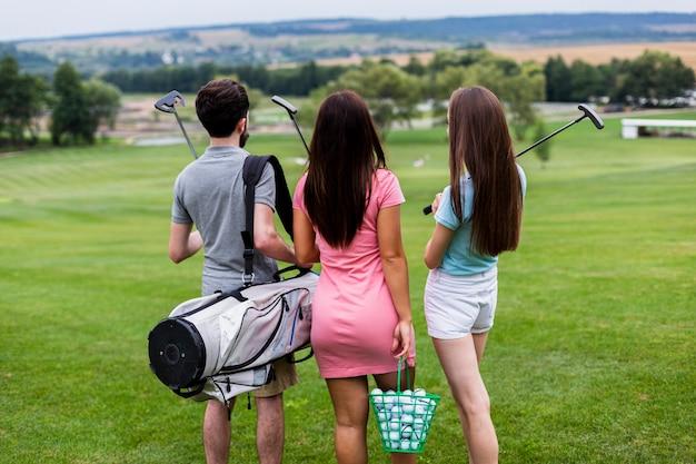 Vista traseira de amigos com equipamento de golfe