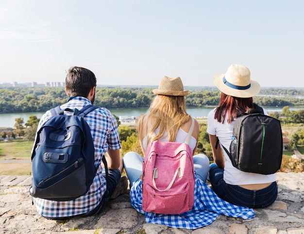 Vista traseira, de, amigos, com, mochila, sentando, ao ar livre