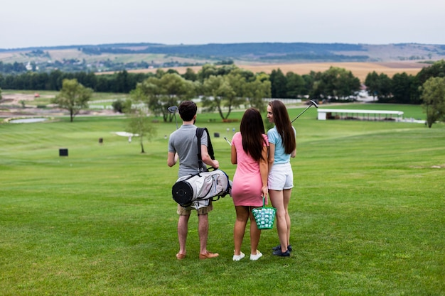 Vista traseira de amigos no campo de golfe