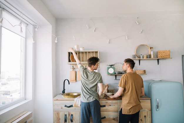 Vista traseira, de, amigos, preparando alimento, em, cozinha doméstica