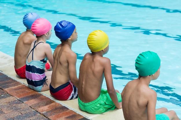 Vista traseira de amigos sentados à beira da piscina