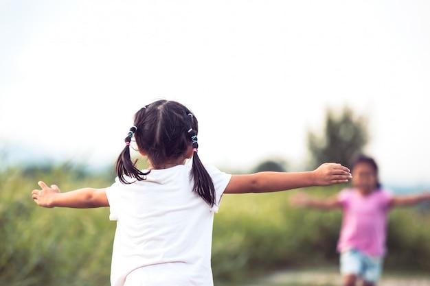 Vista traseira, de, asian, menininha, levantar, dela, mão, e, esperando, dela, irmã, abraçar, um ao outro
