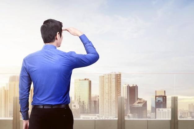 Vista traseira, de, asiático, homem negócios, olhar, cidade moderna