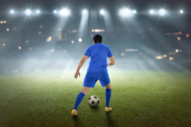 Vista traseira, de, asiático, jogador de futebol, com, a, bola