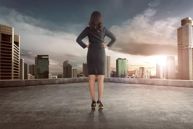 Vista traseira, de, asiático, mulher negócio, olhar, vista pôr do sol
