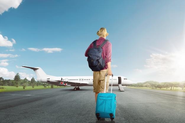 Vista traseira, de, asiático, viajante, andar homem, com, mala, para, avião