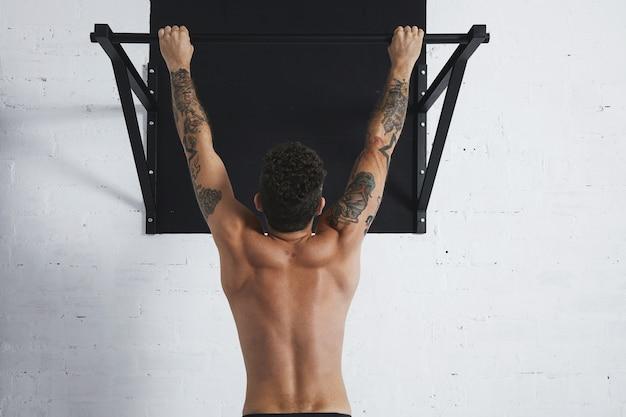 Vista traseira de atleta masculino musculoso em topless mostrando movimentos calistênicos pendurado na barra de tração