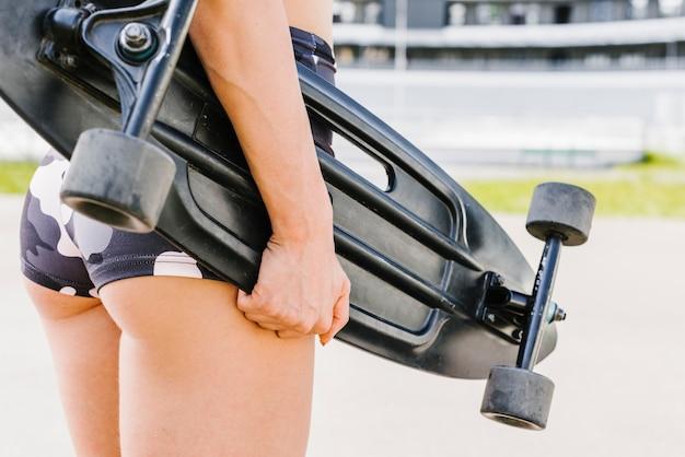 Vista traseira, de, atleta, segurando, longboard