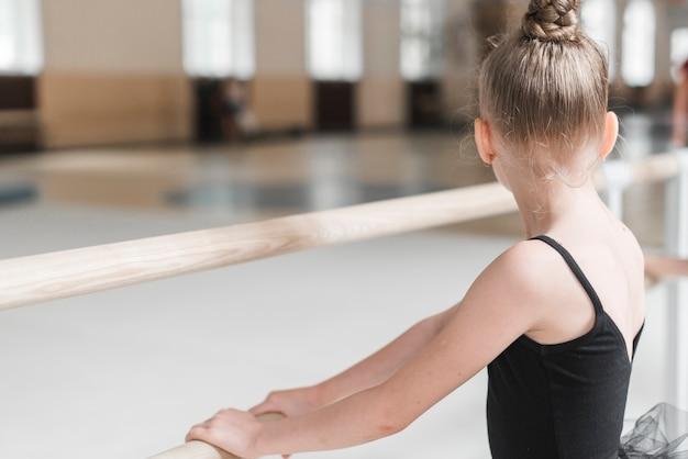 Vista traseira, de, bailarina, menina, segurando, barra madeira