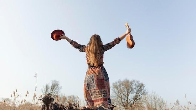 Vista traseira, de, boêmio, mulher segura, teve, e, ukulele