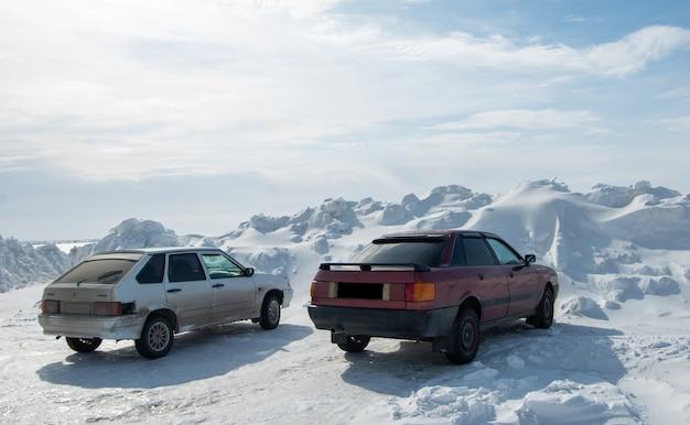 Vista traseira de carros parados perto de um enorme monte de neve formado após limpar as estradas da neve. altas nevascas após uma nevasca. o conceito de limpar estradas de neve