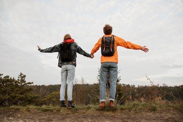 Vista traseira de casal apreciando a vista durante uma viagem