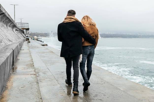 Vista traseira de casal caminhando abraçado na praia no inverno