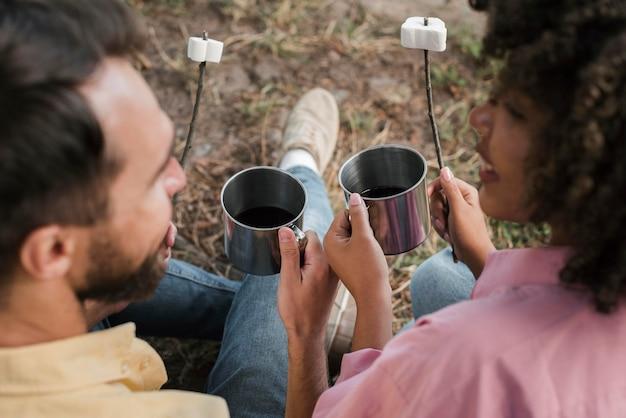 Vista traseira de casal comendo marshmallows durante o acampamento
