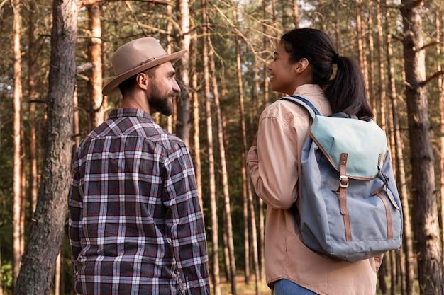 Vista traseira de casal dando um passeio na floresta