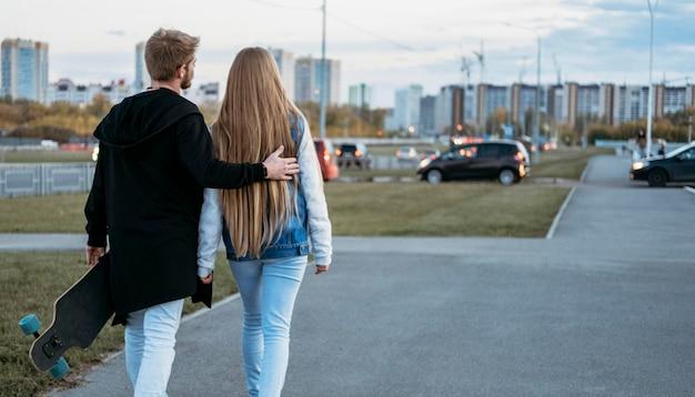 Vista traseira de casal em uma caminhada pela cidade