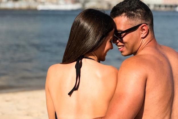Vista traseira de casal romântico na praia