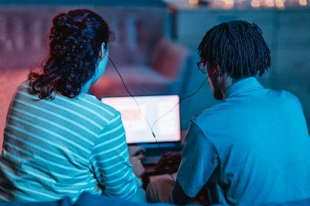 Vista traseira de casal usando laptop e fones de ouvido em casa