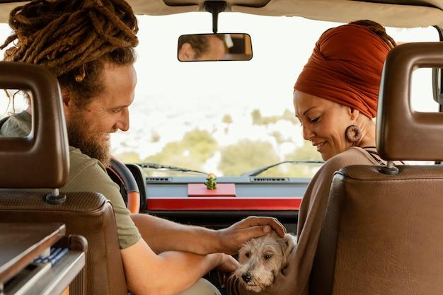 Vista traseira de casal viajando com cachorro