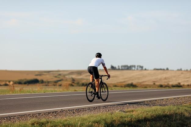 Vista traseira de ciclista profissional em bermuda branca e calção preto andando de bicicleta em estrada pavimentada