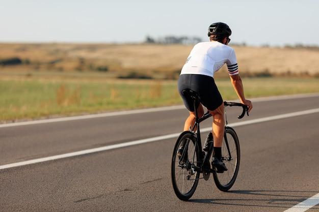 Vista traseira de ciclista profissional em roupas esportivas e capacete de bicicleta em estrada de asfalto