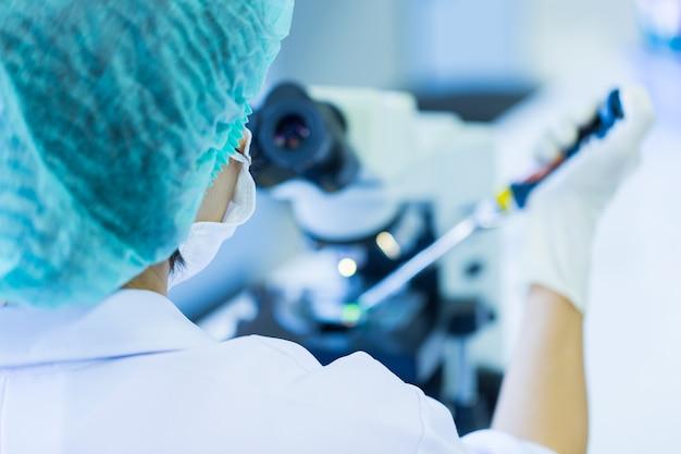Vista traseira, de, cientista, usando, um, microscópio, em, um, laboratório