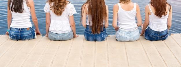 Vista traseira de cinco jovens, vestindo jeans e camiseta branca
