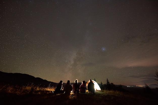 Vista traseira de cinco pessoas sentadas na barraca do turista no espaço da cópia do céu escuro estrelado.