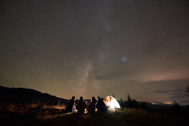 Vista traseira de cinco pessoas sentadas na barraca do turista