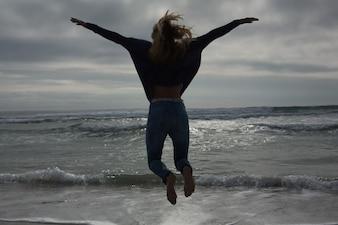 Vista traseira de comprimento total de uma mulher pulando na praia