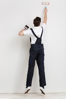 Vista traseira de corpo inteiro da parede de pintura do jovem construtor masculino com rolo de tinta sobre a parede cinza