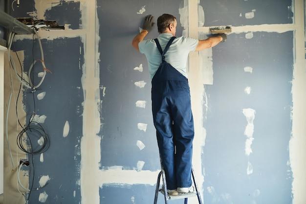 Vista traseira de corpo inteiro de trabalhador da construção civil sênior alisando a parede seca em pé na escada enquanto reforma a casa, copie o espaço
