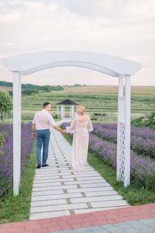 Vista traseira de corpo inteiro de um simpático casal de meia-idade, caminhando no caminho no campo de lavanda, de mãos dadas e se divertindo muito