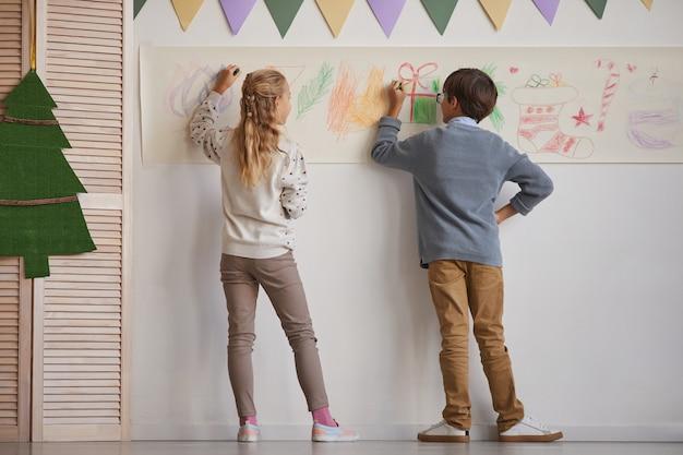 Vista traseira de corpo inteiro para menino e menina desenhando nas paredes enquanto desfruta da aula de arte na escola, copie o espaço