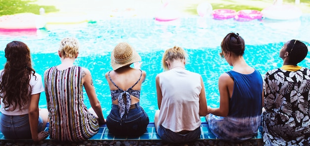 Vista traseira, de, diverso, mulheres, sentando, pela piscina, junto